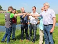 Waterschapbestuurders en melkveehouders brengen een toost uit met slootwater op een succesvolle Proefpolder
